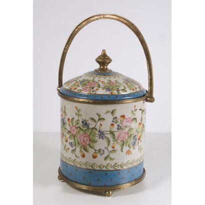 Bello recipiente decorativo con tapa y asa, realizado en porcelana policromada con apliques en bronce dorado, cuenta con una bella decoración floral sobre fondo blanco de la casa