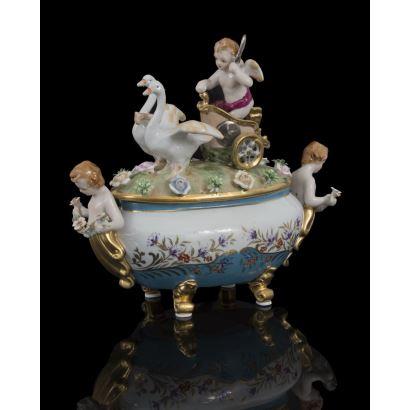 Elegante bombonera  realizada en porcelana,  destaca la tapa decorada en bulto redondo con la imagen de Cupido sobre un carro tirado por cisnes, el cuerpo presenta medallones con escenas mitológicas sobre fondo azul. Medidas: 25,5x27x12cm.