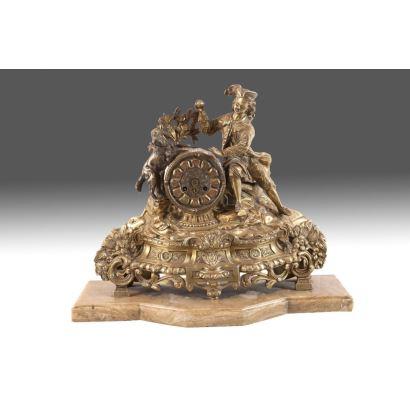 Reloj de sobremesa en bronce dorado sobre peana de mármol.