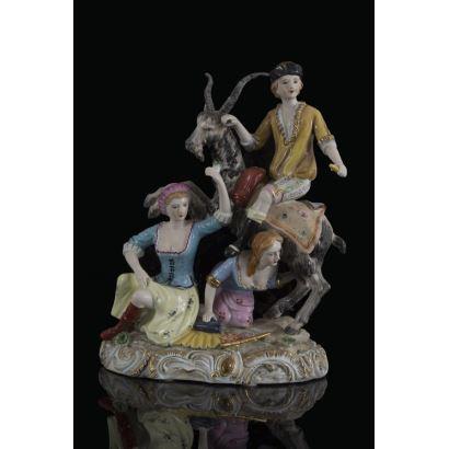 Curioso centro realizado en porcelana ricamente policromado, en él vemos una escena pastoril en la que una pareja de mujeres ordeña a una cabra mientras un joven se sienta sobre su lomo. Marca en base. 31x23x15cm.
