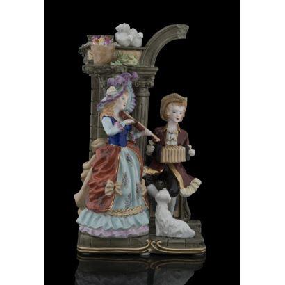 Bonita figura en porcelana policromada, representa a una pareja de músicos ataviados a la moda dieciochesca tocando bajo un medio arco en ruinas. Marca en base. Medidas: 31,5x18,5x11cm.