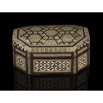 Cajita con estructura de madera con forma octogonal, está decorada con taracea de nácar, ébano y hueso que forman motivos coptos, árabes y judíos, con interior forrado en terciopelo. Medidas: 13x9cm.