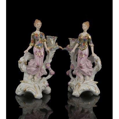 Pareja de candeleros en porcelana policromada, con figuras en bulto redondo de damas de inspiración modernista y brazo de roleo vegetal. Alto: 26cm.