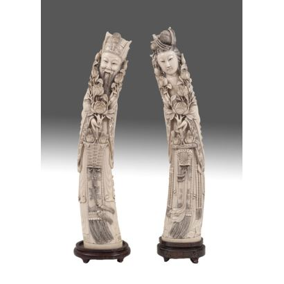 Importante pareja de figuras ricamente talladas en marfil sobre peana de madera. China.