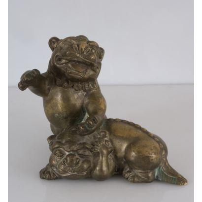 Curiosa y antigua  figura en bronce dorado, en ella contemplamos a una pareja de perros de Fu. Sello en base. 16x20cm.