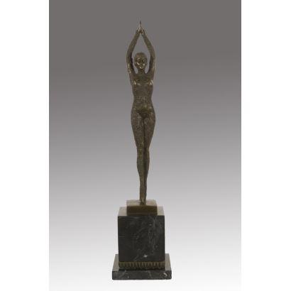 Figura en bronce Art Decó, en ella contemplamos la imagen de una bailarina con los brazos en alto sobre peana cuadrada. 48x11x11cm.