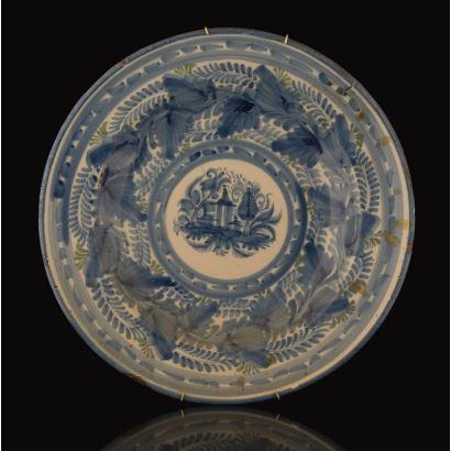 Plato de cerámica de Manises del siglo XIX, con decoración vegetal en azul sobre fondo blanco. Diámetro: 34,5cm.