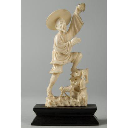 Talla costumbrista de marfil de carácter popular que representa a un campesino chino subiendo una piedra acompañado por su perro. El peregrino se asienta sobre base de madera de doble trapecio. 12cm, sin peana 10x4cm