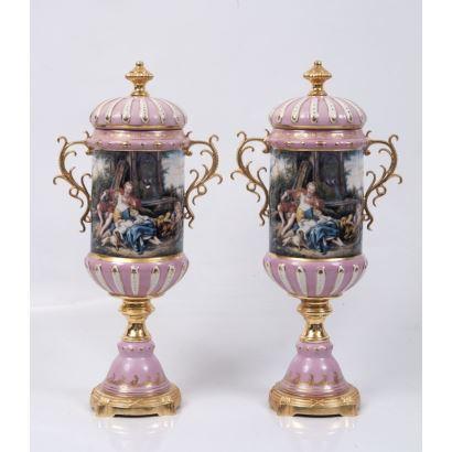 Pareja de jarrones cilíndricos con tapa, en porcelana policromada y bronce dorado y pie y asas, decorados con escenas galantes sobre fondo rosa. Marca en base. Medidas: 50x22cm.