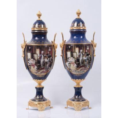 Pareja de jarrones en porcelana policromada en azul y apliques en bronce dorado, decorados con dos escenas: