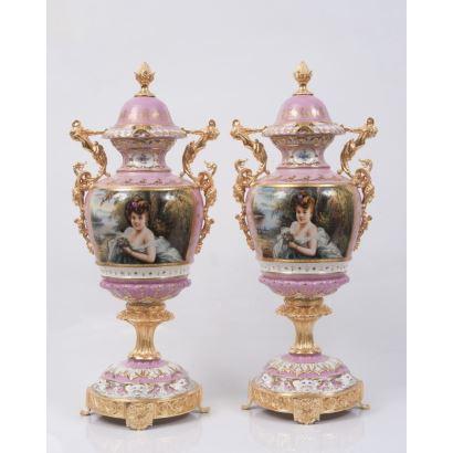 Pareja de jarrones en porcelana policromada sobre fondo rosa, con pie y asas en bronce dorado, presentan retratos de damas entre flores. Marca en base. Medidas: 64x28cm.