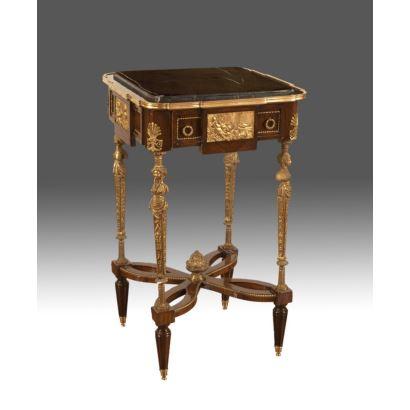 Velador con tablero cuadrado de mármol jaspeado, madera y ricos apliques en bronce dorado en patas a modo de estípite con bustos y escena clásica en faldón sobre cajón, patas unidas en chambarana. Medidas: 87x53x53cm.