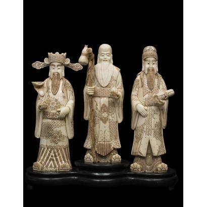 Ante nosotros tres deidades masculinas chinas realizadas en hueso sobre peana, destaca el detallismo en túnica y atributos: cetro, pergamino y bastón'. Medidas: 48cm sin peana: 40x14cm.