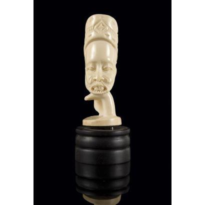 Curiosa cabeza de personaje masculino barbado en marfil africano sobre  peana de madera. 13x5,5cm s/p 10x4,5cm.