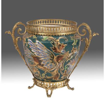 Macetero en porcelana policromada con motivos florales sobre fondo verde, con doble asa de roleo, pie y boca calados en bronce dorado. Medidas: 29x40cm.
