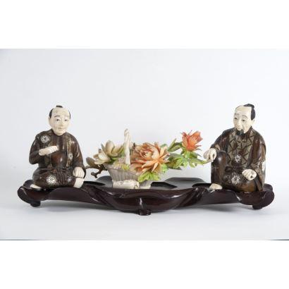 Grupo escultórico oriental realizado en madera y  marfil policromado sobre pedestal, representa a dos hombres entorno a cesta con flores. Principios del siglo XX. Medidas: 15x36x9cm.
