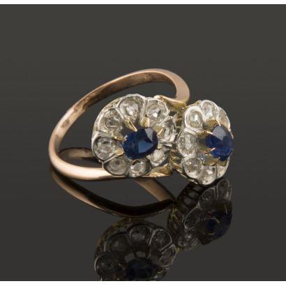 Antiguo anillo tu y yo de oro 18K formado por dos rosetas con zafiros centrales rodeados de diamantes talla rosa. Total aproximado 0,64 quilates. Peso:  4,20 gr.