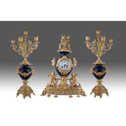 Reloj de sobremesa francés, en bronce dorado al oro fino y porcelana policromada en azul cobalto, con guarnición de jarrones y decoración de cupidos. Esfera firmada: PHILIPPE FabT.   Reloj: 56x40x14cm. Jarrones: 56cm.