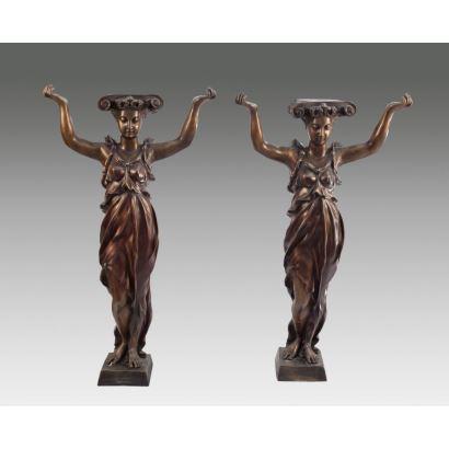 Pareja de esculturas de bronce a modo de peana, representan a una pareja de Cariátides con los brazos en alto y capiteles sobre su cabeza. Medidas: 70x40cm.