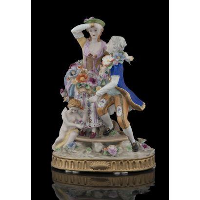 Bonita figura en porcelana policromada, con escena galante de hombre y mujer cubiertos de flores con Cupido a sus pies. Medidas: 32x22,5x15,5cm.