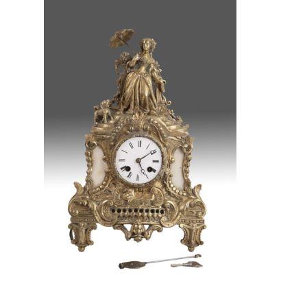 Reloj de sobremesa francés en bronce dorado y mármol, s.XIX, con péndulo y llave. Rematado con la figura de dama sujetando sombrilla. Estado en marcha. Medidas: 40x20cm.