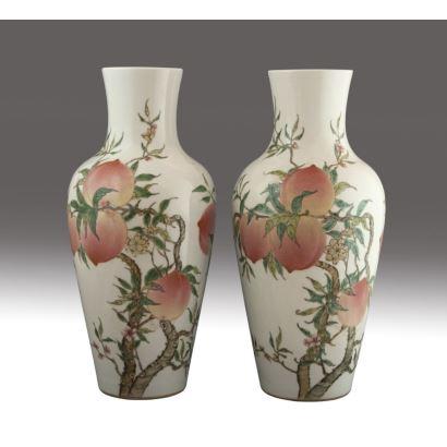 Pareja de jarrones en porcelana esmaltada, China, hacia 1900. Decoración policromada de ramas con melocotones sobre fondo blanco. Marcas en la base. Medidas: 38 x 18 x 18 cm.