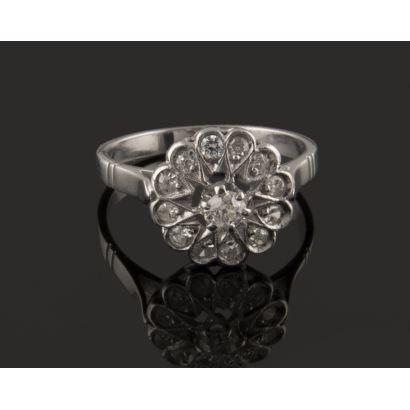 Preciosa sortija rosetón en oro blanco de 18K, con diamante central de 0,15 quilates, talla brillante antigua, orlado por bisel de 0,24 quilates en 12 diamantes engarzados en bocas decoradas en forma de pétalo y garras. Peso: 3,58 gr.