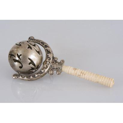 Objetos. Sonajero antiguo realizado en plata con mango de marfil torneado, la bola con motivos calados presenta formas vegetales. 11x4cm.