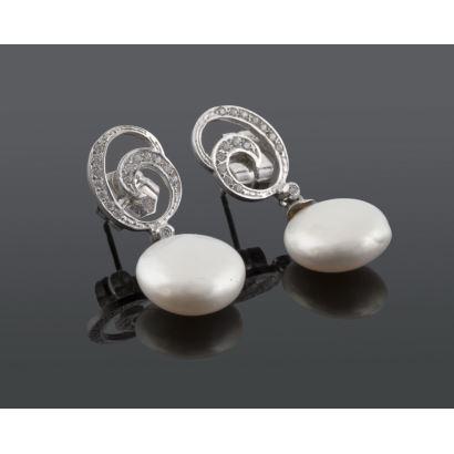 Originales pendientes de espiral en oro blanco con circonitas, de ellos penden perlas. Peso: 4,1g.