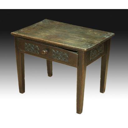 Mesa tocinera española en madera de pino, pps. XIX. Patas rectas y cajón en cintura. Decoración geométrica tallada en cintura. Medidas: 56 x 50 x 72 cm.
