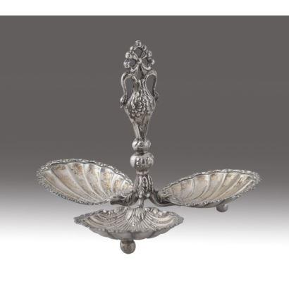 Centro de mesa realizado en plata, con tres platos a modo de venera unidos en parte central por astil de cisnes. Principio siglo XX. Medidas: 17x18x18cm.