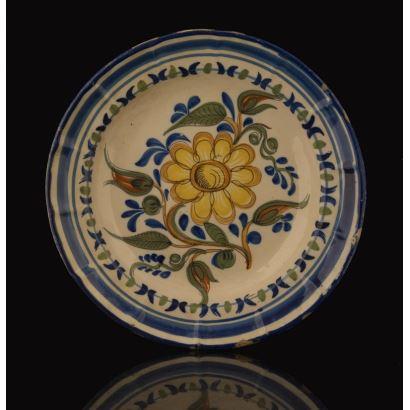Plato de cerámica de Manises del siglo XIX, con bonita decoración de flor amarilla, esta orlado por una doble franja circular en azul. Leves desperfectos. Diámetro: 31cm.