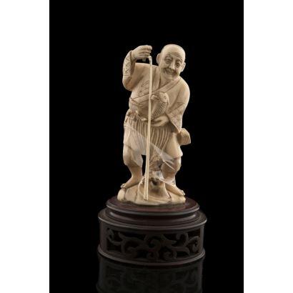 Figura tallada en marfil sobre peana calada de madera.