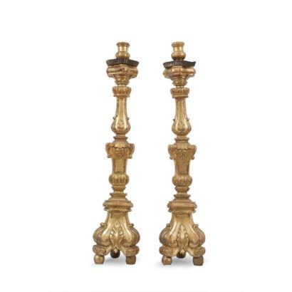 Pareja de hacheros, Carlos IV. Realizados en madera tallada y dorada. Presentan vástago abalaustrado y base triangular. Decoración con motivos de acantos y roleos. Altura: 102 cm.