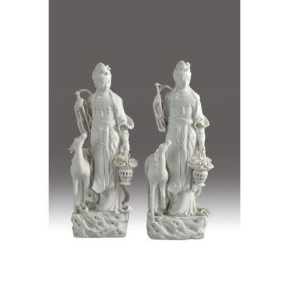 Pareja de diosas chinas en porcelana esmaltada blanc de chine, circa 1900. Ambas portando cestos de flores y con cierno a sus pies. Altura: 28 cm.