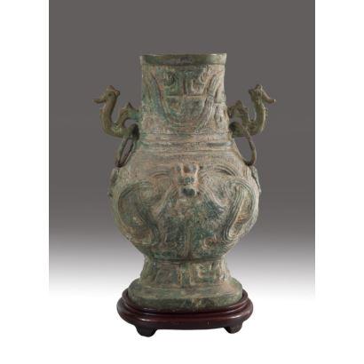 Jarrón chino en bronce, estilo arcaico, circa 1900. Decoración geométrica en el cuerpo y asas en forma animal. Con peana de madera. Medidas con peana: 43 x 29 x 17 cm. Medidas sin peana: 38 x 29 x 14 cm.