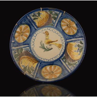 Plato de cerámica de Manises, s.XIX. decorado con ave amarilla en parte central y medallones vegetales dentro de franja azul. Leves desperfectos en borde. Diámetro: 28cm.