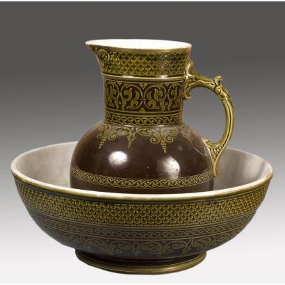 Magnífico aguamanil y jarro, ambos  realizados en cerámica policromada marrón con motivos geométricos y de roleos en amarillo tanto en la boca de la jarra y aguamanil. Aguamanil: 38,5x14cm, jarra 30x14cm.