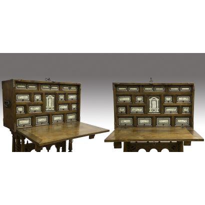 Muebles. Magnífica pareja de bargueños de muestra cubierta en madera de nogal  y placas de hueso grabadas con diversos motivos, destaca por su magnífico trabajo de forja en cerraduras, asas y esquinas, sobre pie de puente. Bargueño: 55x95x39cm Mesa: 88x78x41cm.