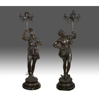 Bronces. Gran pareja de torcheros venecianos realizados en bronce, sujeta cada personaje un candelabro, destaca riqueza decorativa en vestimenta.  Firma en base: A.LUCIGA. Pareja 190x65x65 cms.