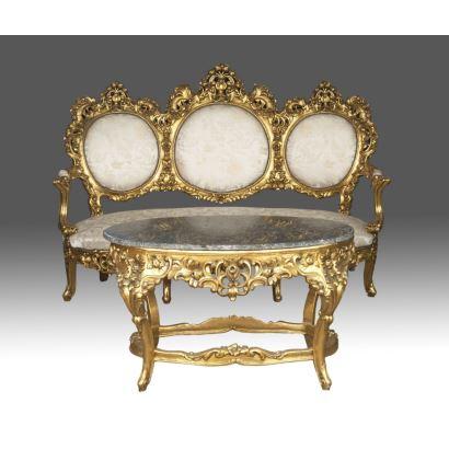 Conjunto de sofá de tres plazas y mesa auxiliar oval, en madera tallada y dorada con rica decoración vegetal, con tapicería color marfil y mesa con tablero de piedra. Medidas sofá: 128x184x70cm; mesa: 63x105x65cm.