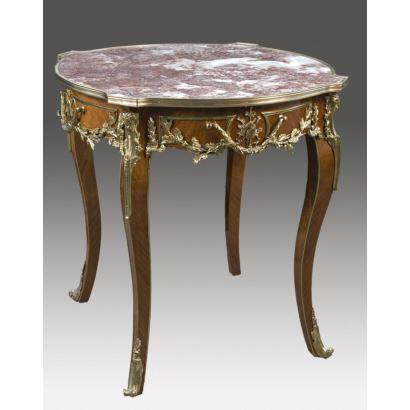 Velador realizado en madera con tapa de mármol jaspeado y apliques en bronce dorado, rica decoración de rocalla y motivos vegetales sobre patas cabriolé. Estilo Luis XV, s.XX. Medidas: 80x77x77cm.