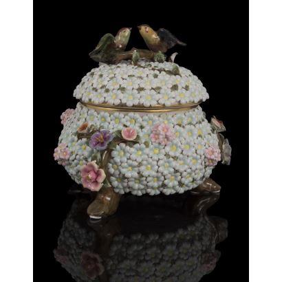 Bonita bombonera con tapa,  cubierta por flores azules y rosas en relieve y asa con aves. Medidas: 25x26x26cm.