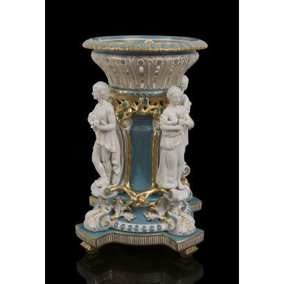 Elegante centro de mesa en porcelana policromada con fondo azul y blanco con detalles en dorado, la base representa en bulto redondo figuras de alegorías clásicas en blanco. Medidas: 49x30,5cm.
