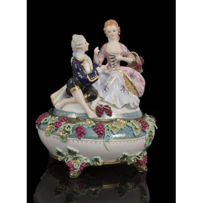 Bombonera en porcelana policromada, con excepcional tapa que alberga una escena galante dieciochesca protagonizada por un caballero y una dama con racimos de uvas. Medidas: 30x25,5x22cm.