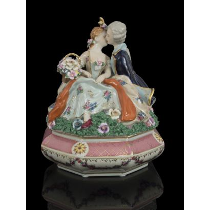 Bonita bombonera con tapa en porcelana rosa y blanca con guirnaldas y detalles en dorado, destaca la tapa con pareja de enamorados de gusto dieciochesco. Medidas: 31x26x26cm.