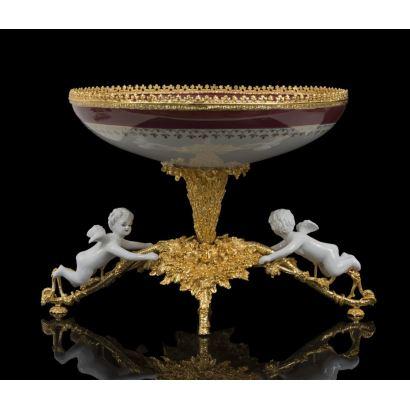 Magnífico centro de mesa con forma en copa en porcelana policromada en granate  y blanco, con pie y borde en bronce dorado al oro fino en el que se posan dos amorcillos alados en blanco. Alto: 26cm.