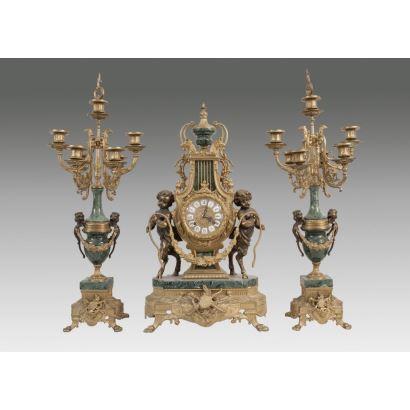 Reloj de sobremesa estilo Luis XVI, cuenta con guarnición de candelabros en mármol verde jaspeado  y bronce dorado, con decoración de niños fauno. Reloj con forma de lira. Alto: 62cm.