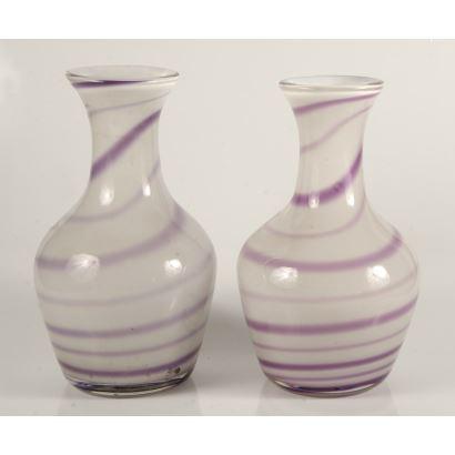Original pareja de jarrones realizados en cristal soplado, ambos con fondo blanco rodeado por una  espiral morada. 33x14cm.