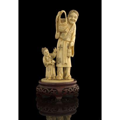 Bella talla de gusto costumbrista, representa con gran expresividad a un anciano sujetando una cesa acompañado por una niña. Con certificado de antigüedad. Alto: 17cm.